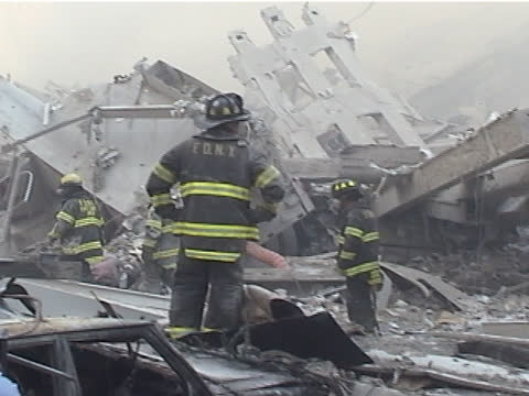 view from liberty st and west st. firemen walk on rubble, damaged fire truck, a man covers human remains with blanket and walks away during the late... - september 11 2001 attacks stock videos & royalty-free footage