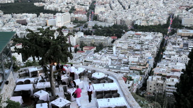 view from lykavittos hill overlooking a restaurant and the beautiful city of athens,  greece, europ - lycabettus hill stock videos & royalty-free footage