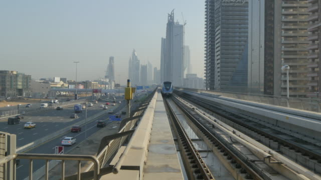 View from Metro Station of train approaching and Sheikh Zayed Road in Downtown, Dubai, United Arab Emirates, Middle East, Asia