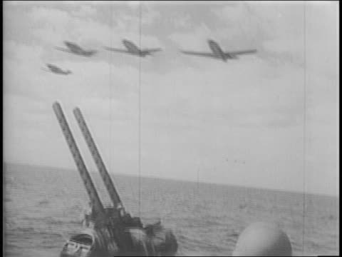 view from moving boat of planes flying overhead / soldiers on boat next to antiaircraft gun / view of spray from back of boat / line of boats with... - flugabwehr stock-videos und b-roll-filmmaterial