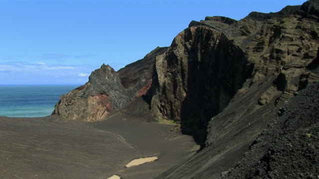 ws pan view from new territory which has been created by the eruption from 1957 / ponta dos capelinhos, faial island, azores, portugal - アゾレス諸島点の映像素材/bロール