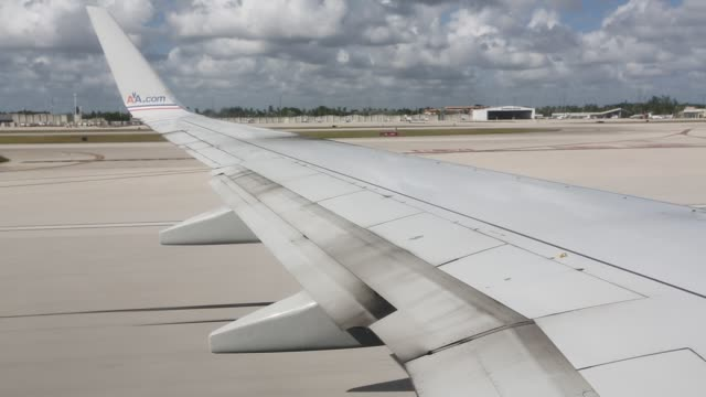 view from onboard the plane through the window of the plane's wing as it takes off from miami airport in florida, united states of america on october... - moving activity stock videos & royalty-free footage