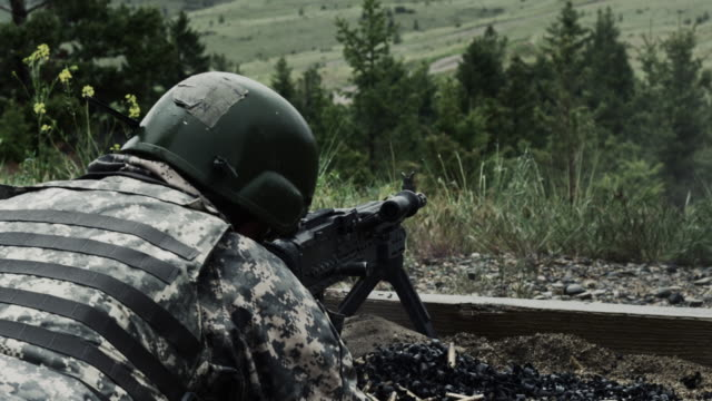 view from over the shoulder of a soldier as he is shooting a belt-fed machine gun. - army helmet stock videos & royalty-free footage