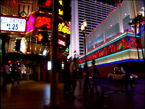 view from passing car tracking left and looking out to neon lights and entertainment venues, las vegas - casino stock videos & royalty-free footage