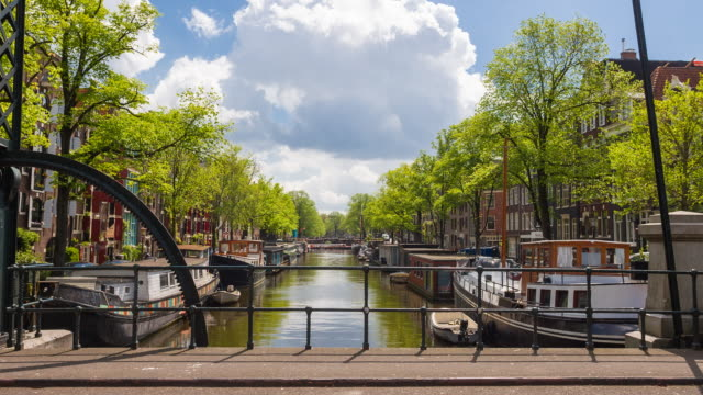 view from personal perspective of amsterdam river canal with boats and boathouses from a bridge - amsterdam video stock e b–roll