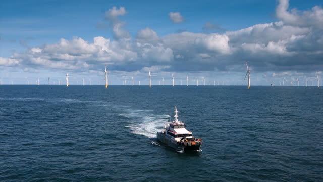 vídeos de stock, filmes e b-roll de vista da plataforma no navio transfer (barco, cais) está vindo em direção a turbina eólica offshore, pegar técnicos, mar ondulado azul e céu mal-humorado, dramático, parque eólico no horizonte - mar do norte