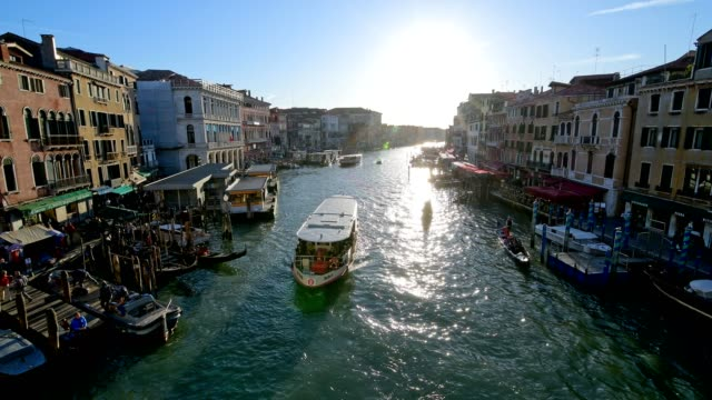 view from rialto bridge over grand canal with vapretto and sun, venice, venetian lagoon, veneto, italy - tourism stock videos & royalty-free footage