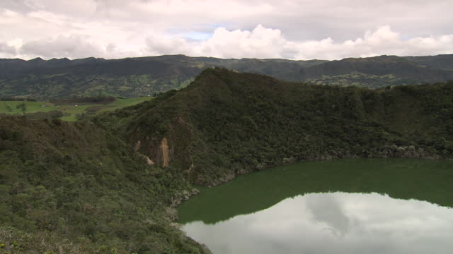 View from ridge of Laguna De Guatavita edge, with cloudy sky and mountain range in b/g, Cundinamarca region, Colombia