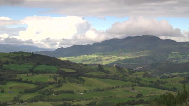 View from ridge of Laguna De Guatavita towards green fields, hills and mountain range, Cundinamarca, Colombia