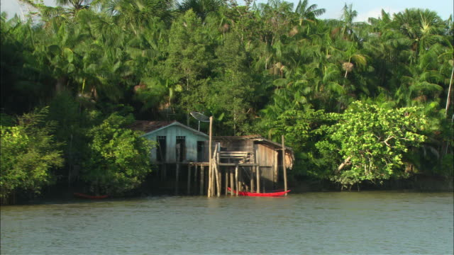 WS View from river of stilt house with red canoe tethered to stilt/ Brazil