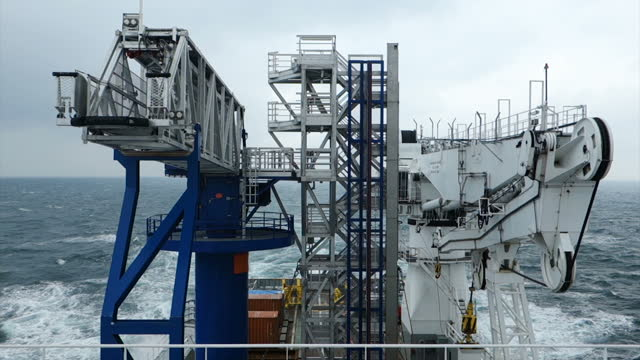 view from roof of transfer vessel (boat, jetty) on boat deck, crane and passenger bridge sailing true north wavy sea, moody sky - railings stock videos & royalty-free footage