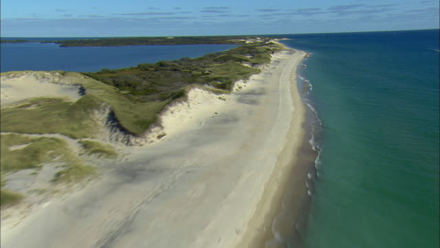 ws pov aerial view from sand dunes and beach of south shore of martha's vineyard to atlantic ocean / martha's vineyard, massachusetts, usa - riva dell'acqua video stock e b–roll