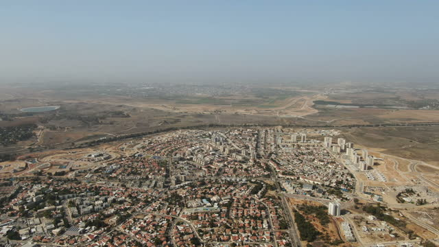 view from sderot city ,gaza envelope towards gaza strip with dry agricultural fields / aerial - negev, israel - ガザ地区点の映像素材/bロール