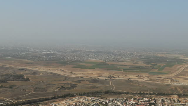 view from sderot city towards border with gaza strip/ aerial - negev, israel - striscia di gaza video stock e b–roll