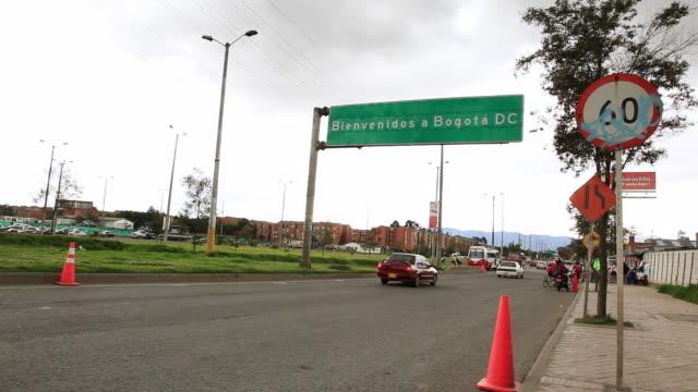 ws la view from sidewalk traffic flows under street sign saying bienvenidos a bogota dc / bogota, colombia - bogota stock videos & royalty-free footage