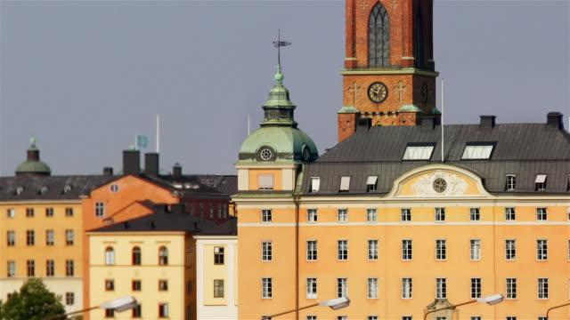 view from sodermalm of clock on steeple of riddarholm church / pull back to view of gamla stan and traffic crossing bridge in fast motion / stockholm, sweden - tornspira bildbanksvideor och videomaterial från bakom kulisserna