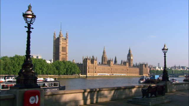 view from south bank of thames of houses of parliament on opposite bank / people jogging and cycling along south bank / london, england - victoria tower stock videos & royalty-free footage
