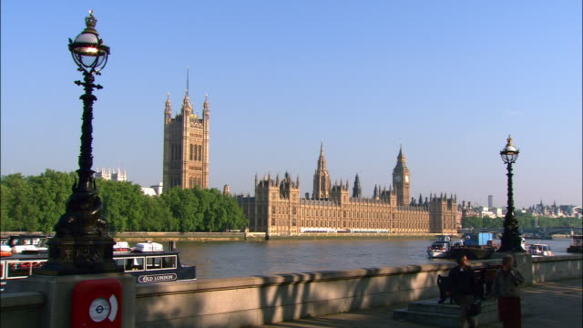 view from south bank of thames of houses of parliament on opposite bank / people walking along south bank / london, england - victoria tower stock videos & royalty-free footage