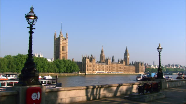 view from south bank of thames of houses of parliament on opposite bank / people cycling and jogging along south bank / london, england - riverbank stock videos and b-roll footage