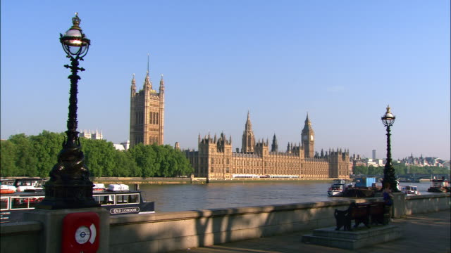 view from south bank of thames of houses of parliament on opposite bank / people jogging, cycling and walking along south bank / london, england - victoria tower stock videos & royalty-free footage