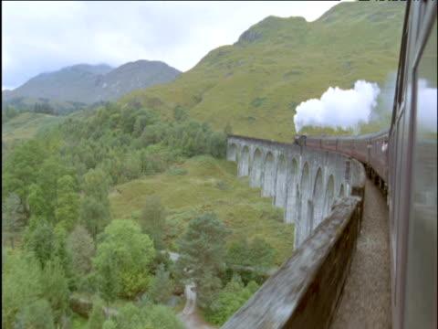 stockvideo's en b-roll-footage met view from steam train as it crosses curved glenfinnan viaduct scottish highlands - ruimte exploratie