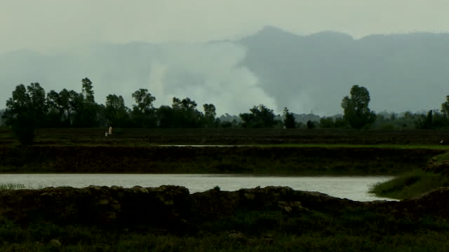 View from the Bangladesh side of the border with Burma of smoke rising from a Rohingya village being burned down