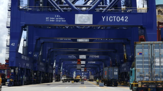 View from the dock of Nansha container port looking towards a row of gantry cranes and the stern of the Gunhilde Maesrsk container ship