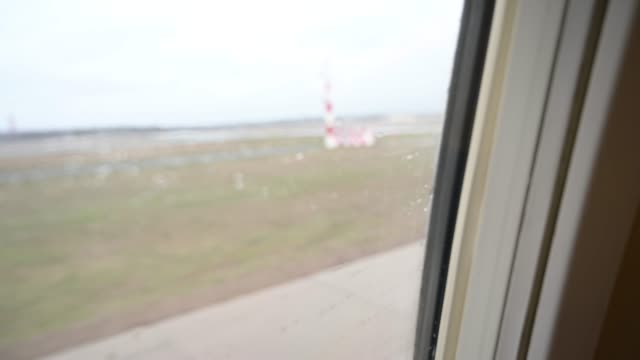 view from the frosted window of an airplane when going by the runway takeoff. a human finger is pointing out something. - human finger video stock e b–roll
