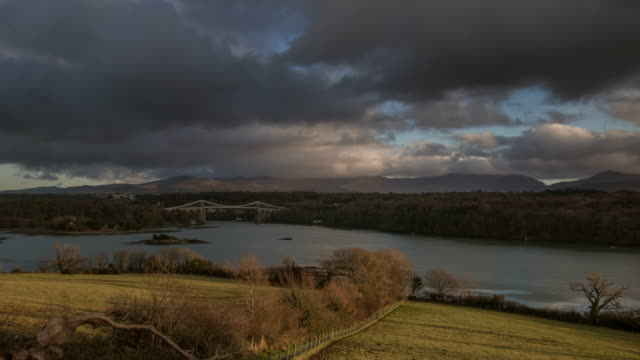 view from the island of anglesey looking over agricultural fields towards the menai strait north wales and the menai suspension bridge - wales stock videos & royalty-free footage
