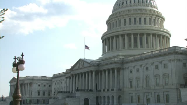 view from the northeast of the east front plaza of the united states capitol building, a us flag floor flying at half mast has late georgia... - georgia us state stock videos & royalty-free footage