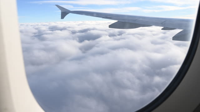 view from the plane window of a landscape full of beautiful clouds under the wing of the plane. - fenster stock-videos und b-roll-filmmaterial