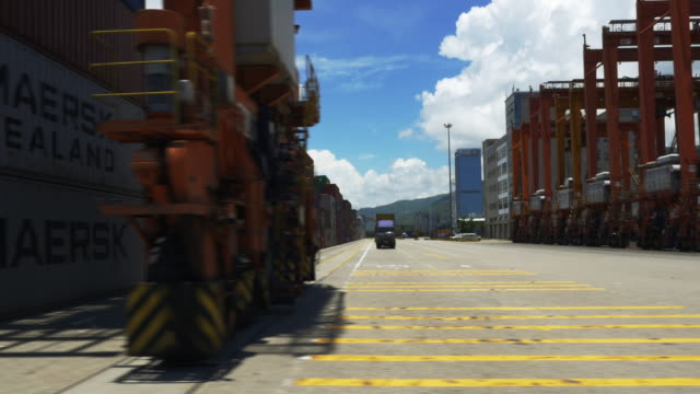 View from the side of a moving vehicle touring slowly through Nansha container dock in China Container ships and rows of stacked containers fill the frame