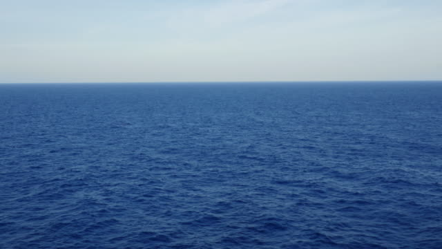 View from the starboard side of a container ship crossing the open blue ocean with a calm surface