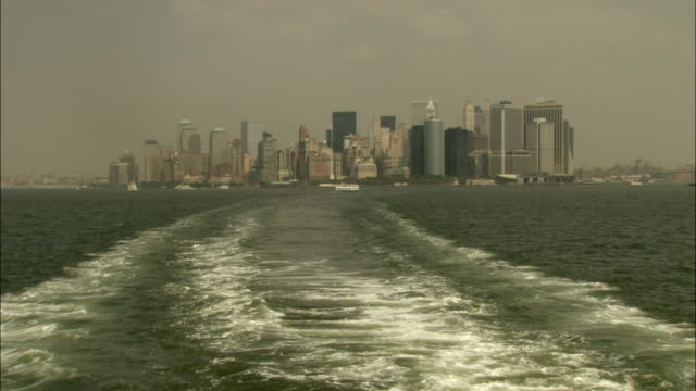 vídeos de stock, filmes e b-roll de view from the stern of a boat crossing new york harbor. available in hd. - porto de nova york