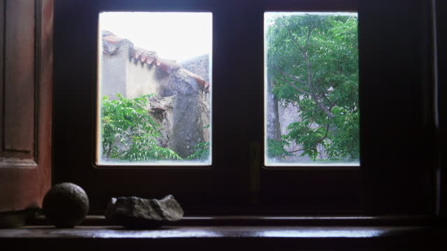 view from the window of an old house in monemvasia with cannon ball from former times - window frame stock videos and b-roll footage