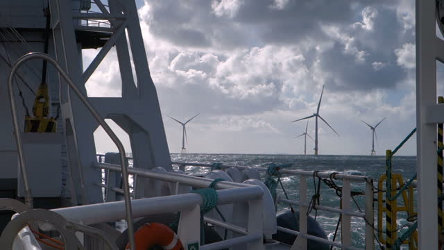 view from transfer vessel (boat, ferry) deck sailing on stormy weather north sea around wind farm. wind turbines on the horizont. dramatic sky, raf sea and sunny. germany and borkum riffgrund wind farm. - blade stock videos & royalty-free footage