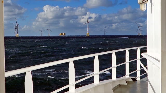 view from transfer vessel (boat, ferry) nose sailing on stormy north sea true wind farm. wind turbines on the horizont. - turbine stock videos & royalty-free footage
