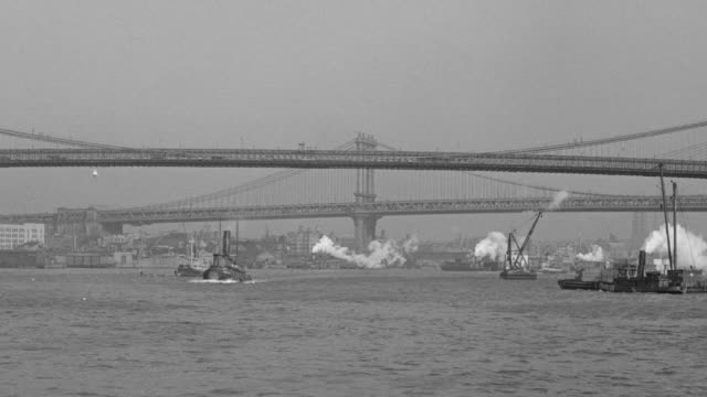 ws pov view from tugboat on east river passing under brooklyn bridge manhattan skyline and multiple boats in river - brooklyn bridge stock videos & royalty-free footage