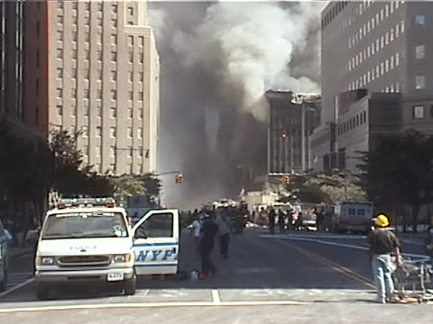 view from vesey st. looking east as the world trade center building six burns two ambulances arrive on vesey st. during the late afternoon on... - september 11 2001 attacks点の映像素材/bロール
