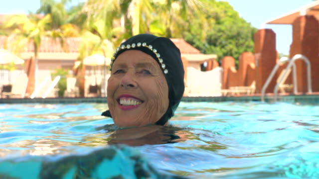 cu view from water of smiling senior female synchronized swimmer hanging out in pool after routine - caucasian appearance stock videos & royalty-free footage