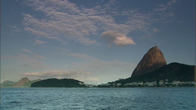 ws pan view from water of waterfront homes and sugarloaf mountain/ rio de janeiro, brazil - riva dell'acqua video stock e b–roll