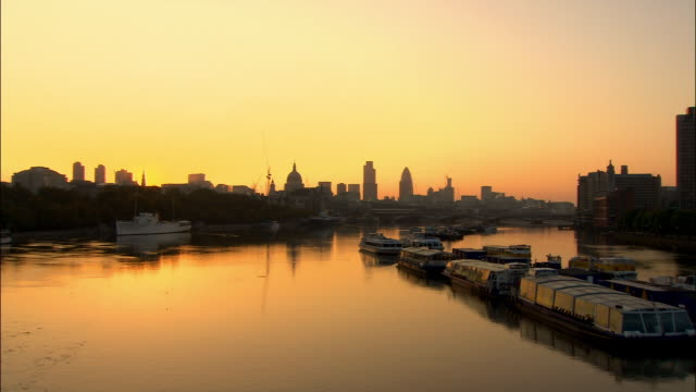 View from Waterloo Bridge of skyline of City of London cast in silhouette at sunrise / London, England