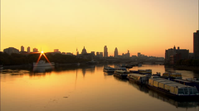 view from waterloo bridge of skyline of city of london cast in silhouette at sunrise / london, england - 2006 stock videos & royalty-free footage
