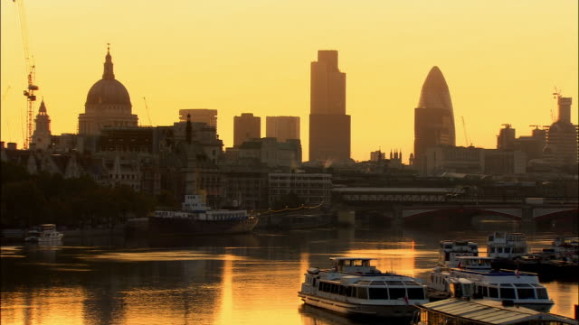 view from waterloo bridge of skyline of city of london cast in silhouette at sunrise / london, england - sir norman foster building stock videos & royalty-free footage