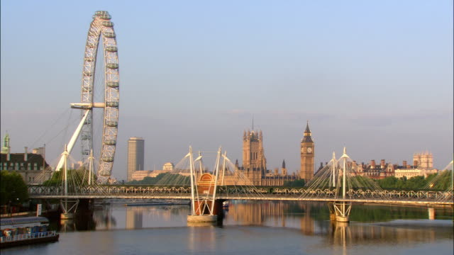 view from waterloo bridge of train crossing hungerford bridge over river thames, houses of parliament, and london eye / london, england - parliament building stock videos & royalty-free footage