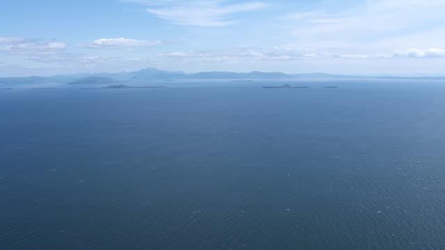 vídeos y material grabado en eventos de stock de ws aerial view high of sea in hebrides on west coast heading towards isles / isle or island of mull and treshnish, isles argyll and bute, scotland - isla de mull