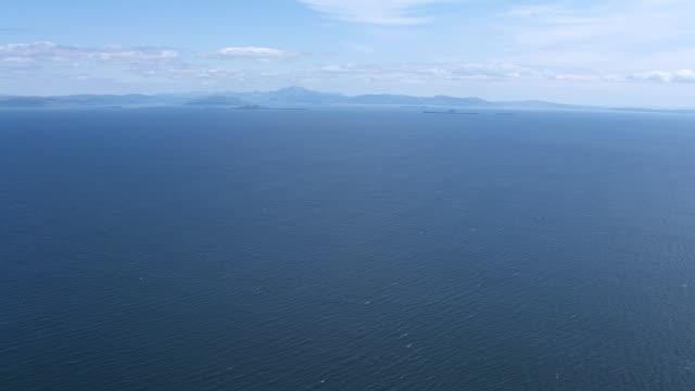 vídeos y material grabado en eventos de stock de ws aerial view high over sea in hebrides on west coast / isle or island of mull and treshnish, isles argyll and bute, scotland - isla de mull