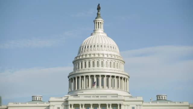 stockvideo's en b-roll-footage met ws view if dome of us capitol building tight and flag blowing in wind / washington, district of columbia, united states - koepel