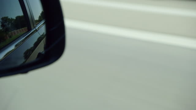 view in mirror while driving on highway - innenspiegel stock-videos und b-roll-filmmaterial