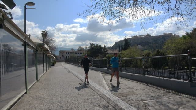 view in the empty street and closed shops due to the ban , while two joggers are running in thiseio area, located under the acropolis, that is one of... - athens greece stock videos & royalty-free footage